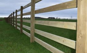 Looking along post and rail fencing Around Equestrian Paddock