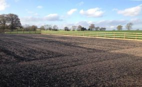 Freshly surfaced riding arena with post and rail fence and blue sky