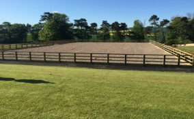 Finely manicured lawn leading to post an rail fence enclosed riding arena
