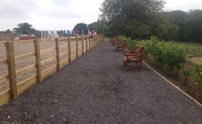 Path outside riding arena with wooden benches