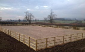 Newly completed riding arena surrounded by post and rail fencing