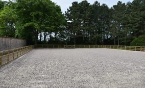 Sand Fibre Equestrian Riding Arena Located In North Yorkshire With Post & Raill Fence Surrounded By Trees & Wall & Blue Sky