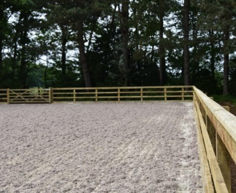 Sand Fibre Equestrian Riding Arena Located In North Yorkshire With Post & Raill Fence Surrounded By Trees