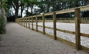 Looking Down Gravel Path With Timber Post & Rail Fence To The Side, All The The Side Of A Equestrian Riding Arena Located In North Yorkshire