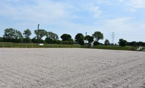 View Looking into the large equestrian, equine riding arena, with sand & fibre surface surrounded by timber post & rail fence with telegraph poles and arena lighting showing. Located In North Yorkshire