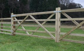 Timber double gates next to post and rail fencing in green field