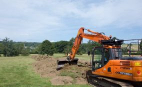 excavator removing turf in field
