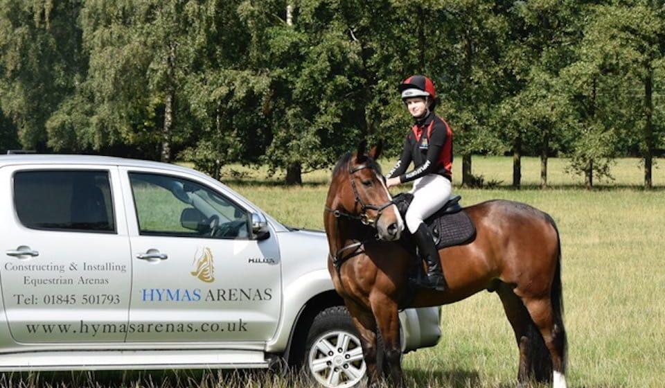 Rider on horse next to Hymas Arenas branded pickup