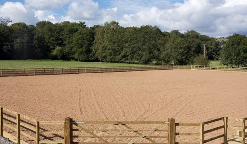 neatly levelled surface of empty equine arena with timber gate