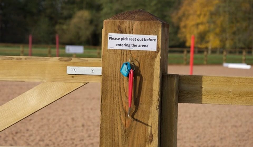 small sign on gatepost of equine arena that reads 'Please pick feet out before entering arena'