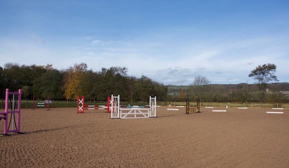 neatly levelled surface of empty equine arena with jumps setup