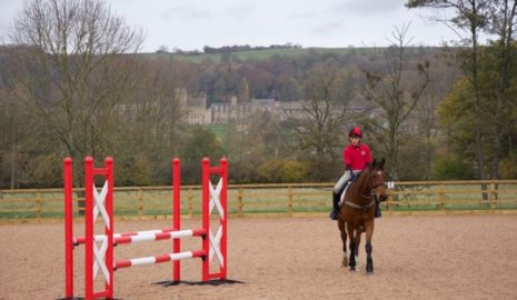 horse and rider in equine arena with Ampleforth college in the background